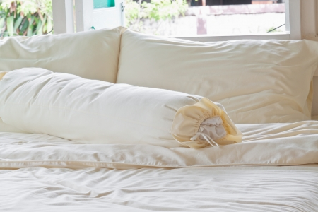 Messy bed with white pillows near windows
