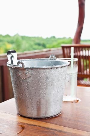 Gota de agua en la cubeta de hielo y la mesa