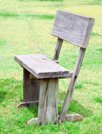 old wooden chair ongreen grass in lawn photo