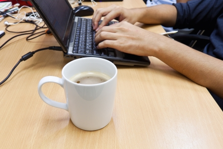 Cup of coffee with hand on laptop  Office interior  photo