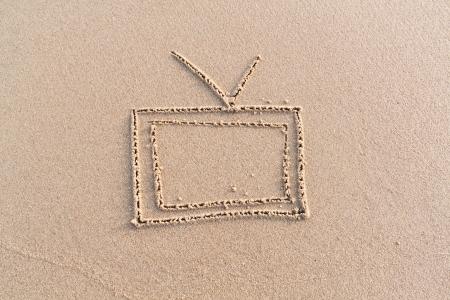 Дать телевидения на песке вручную Фото со стока