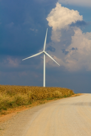 Wind turbine on wind field with cloudy sky photo