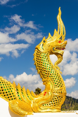 Golden king of Naga in temple with blue sky