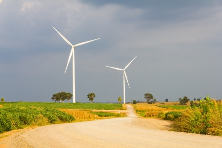 Road to wind turbine field with cloudy sky Stock Photo - 17158205