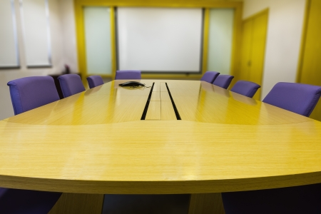 Meeting room with wooden table , armchairs, projector and white board  Office interior photo