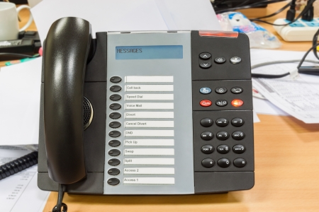 Black modern telephone on table in office photo