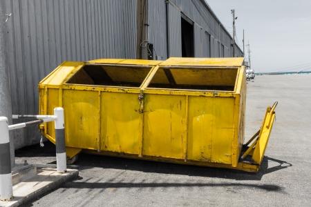Yellow metal waste skip near warehouse 版權商用圖片