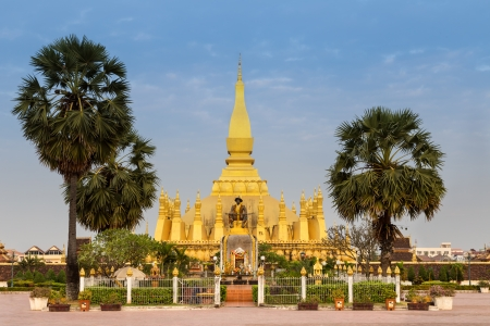 King Setthathirat statue and Pha That Luang stupa in evening
