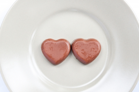 Two heart shape chocolate on white plate Stock Photo