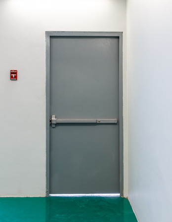 赤い火警報ボタンを持つ金属非常口ドア