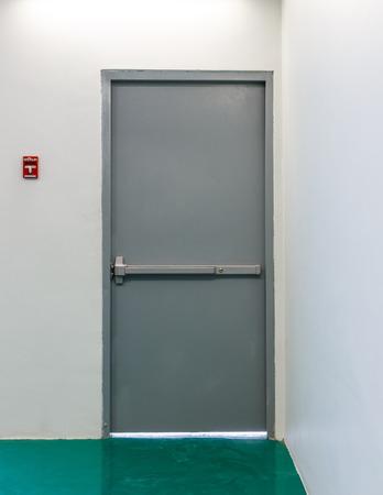 Metal emergency exit door with red fire alarm button