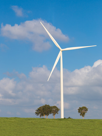 Wind turbine on green field and blue sky photo