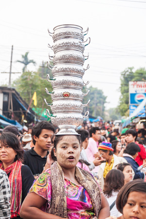 Mon woman carries aluminum jars on her head