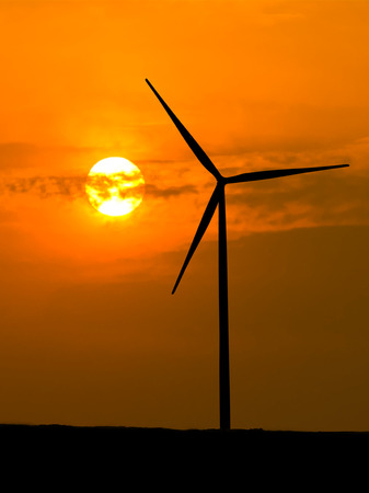 Wind turbine silhouette with sunlight and orange sky photo