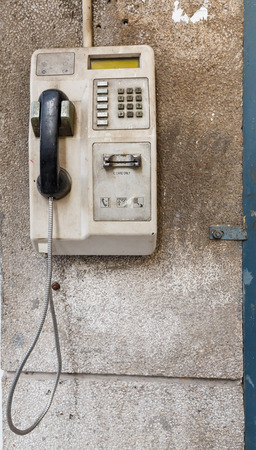 pay wall: Old public telephone on the wall
