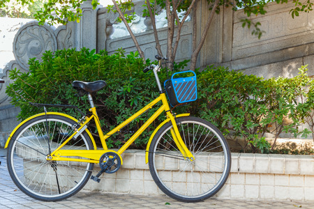 Old yellow bicycle on street in temple Stock Photo