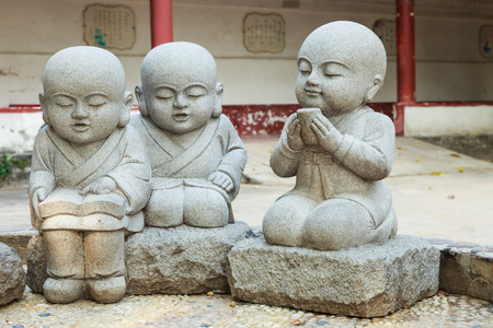Stone statue of learning and relax Chinese monks in temple