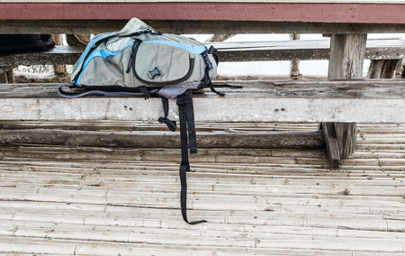 Camera bag on wooden bench for photography