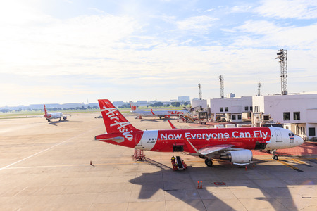 underwing: BANGKOK, THAILAND - 12 SEPTEMBER 2015 - Airbus A320-200 Thai Airasia connected to jetway at Don Muang international airport. Thai Airasia is the low cost airline in Thailand.