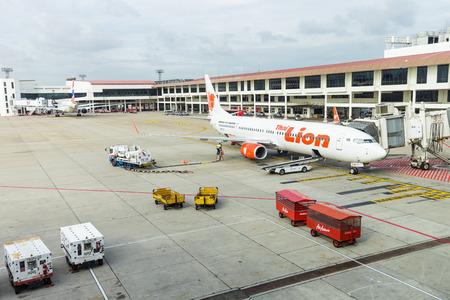 underwing: BANGKOK, THAILAND - 12 SEPTEMBER 2015 - Jet way from terminal to Boeing 737 aircraft at Don Mueang International Airport.