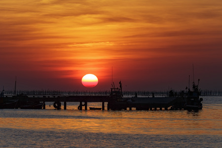 fishing pier: Sunset over sea and silhouette fishing pier