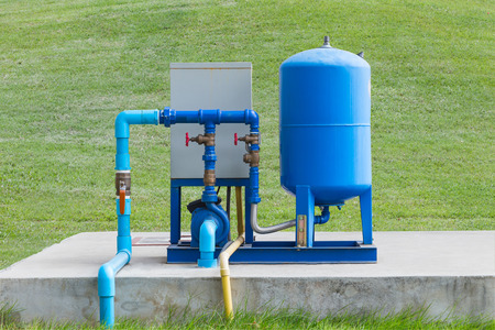 concrete pump: Water pump system on concrete and green grass