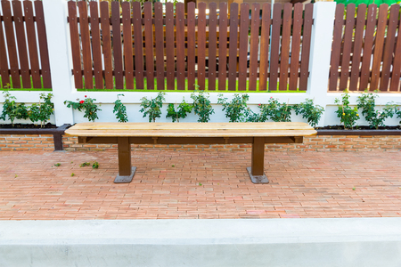 fench: Wooden bench on footpath near wall Stock Photo