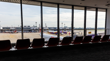 underwing: BANGKOK, THAILAND - 12 SEPTEMBER 2015 - Airplanes connected to jetway at Don Muang international airport.