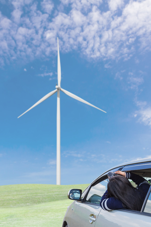 Traveller photographed the wind turbine on grass field with blue sky and white cloud from car