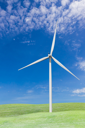 Wind turbines on grass field with blue sky and white cloud from car