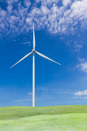Wind turbine on grass field with blue sky and white cloud Stock Photo