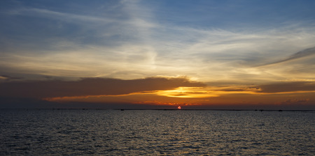 Orange sunset over sea shore and wetland with silhouette shell farm