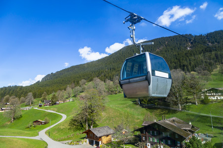 Cable car over small village and hotels on mountain alps, transpotation from grindelwald to First peak switzerland