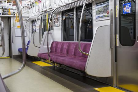 TOKYO ,JAPAN - OCTOBER 13: Passenger seats in Tokyo Japanese metro train , OCT 13,2016, Tokyo, Japan.  Passenger seats in Japanese metro train with nobody Редакционное