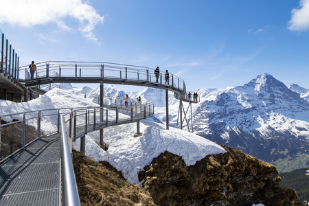 GRINDELWALD BERNE, SWITZERLAND- APRIL 24 : Traveller are resting and photograph on sky cliff walk at First peak of Alps mountain Grindelwald Switzerland 新聞圖片