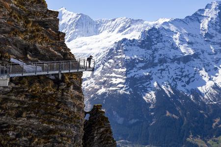 GRINDELWALD BERNE, SWITZERLAND - APRIL 24 : Traveller is taking image on sky cliff walk at First peak of Alps mountain Grindelwald Switzerland