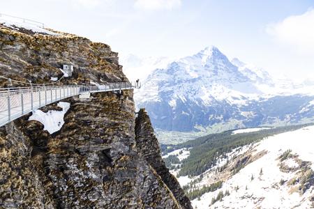 Traveller taking image on sky cliff walk at First peak of Alps mountain Grindelwald Switzerland