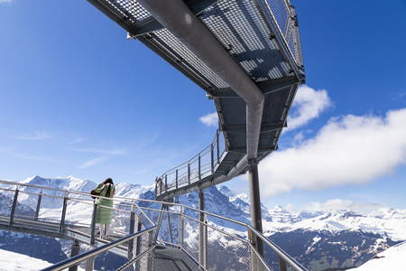 GRINDELWALD BERNE, SWITZERLAND - APRIL 24 : Traveller are resting and photograph on sky cliff walk at First peak of Alps mountain Grindelwald Switzerland