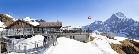 GRINDELWALD BERNE, SWITZERLAND- APRIL 24, 2018 : Traveller are resting and photograph on sky cliff walk at First peak of Alps mountain Grindelwald Switzerland