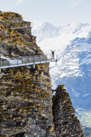 Traveller are walking on sky cliff walk at First peak of Alps mountain, Grindelwald Switzerland, happy man 新聞圖片