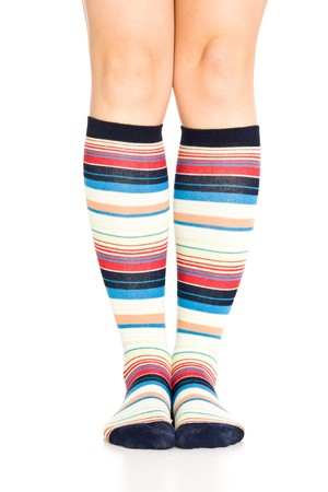 Caucasian woman legs in colorful stripped socks on white isolated background photo