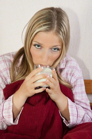 Woman in pajama in bed with glass of milk photo