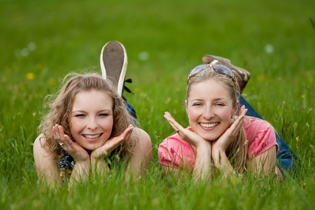 lay: Two sisters lay on the grass