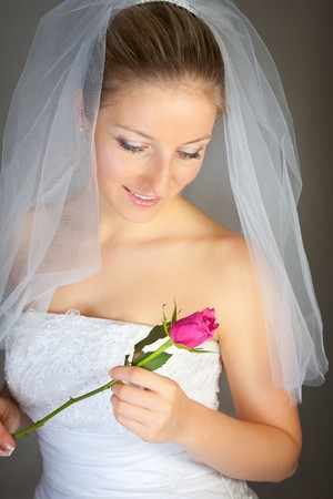 Caucasian bride posing in wedding dress and rose flower