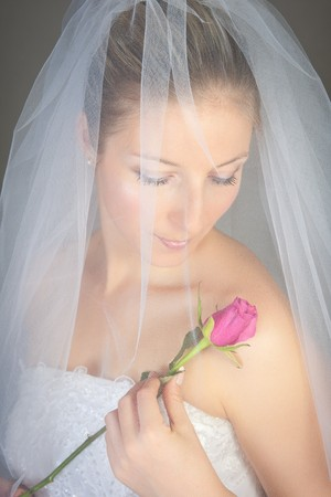 pink posing: Caucasian bride posing in wedding dress and rose flower