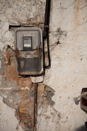 electricity meter: Old electricity meter on battered wall