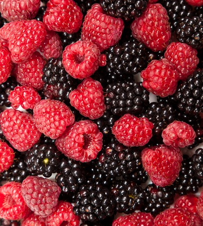 Composition of black and red raspberries on white isolated background in studio photo