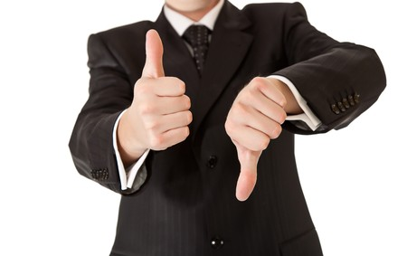 Business man in suit thumbs up and down on white isolated background photo