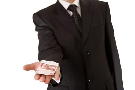 Business man holding money on white isolated background photo