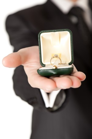 engagement ring: Man in suit holding engagement ring on white isolated background